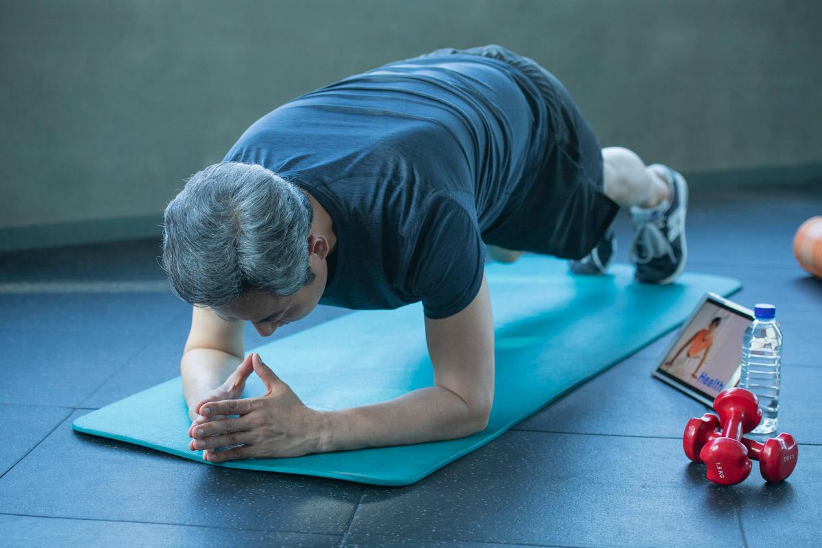 家でトレーニングをしている男性のイメージ写真