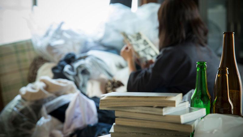 ゴミ屋敷の中で過ごす人のイメージ写真