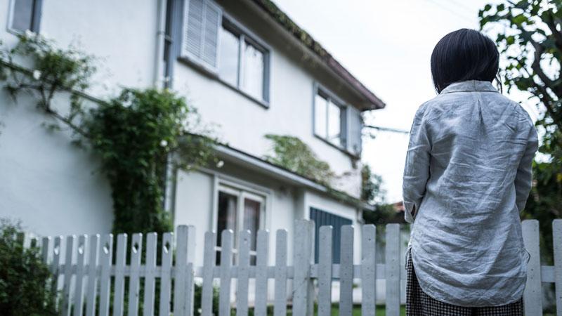 空き家になった家を眺める遺族のイメージ写真